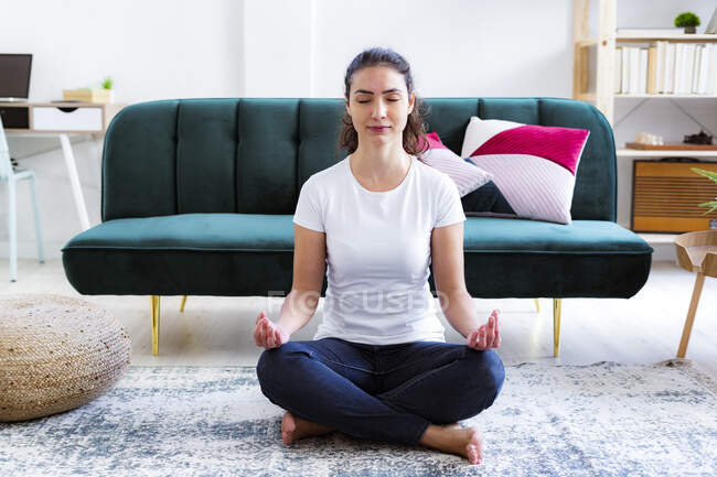 Молодая женщина медитирует, сидя дома — стоковое фото