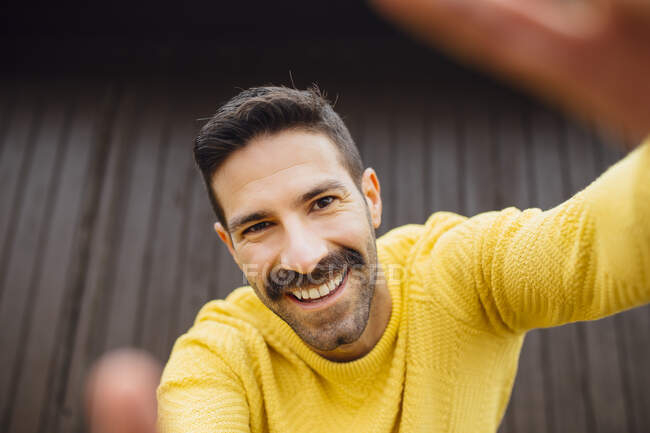 Smiling man with mustache in yellow sweater taking selfie — Stock Photo