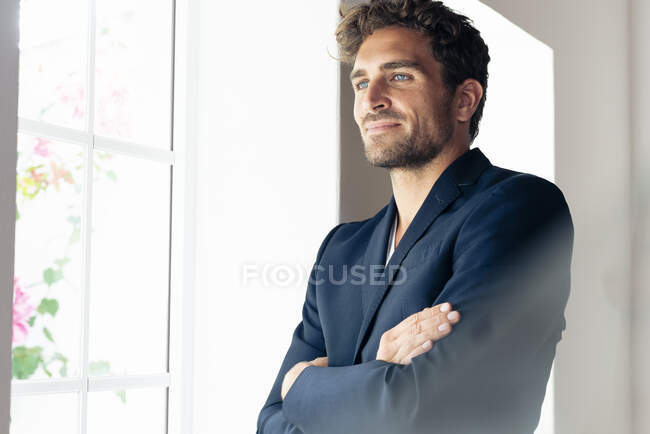 Hombre de negocios adulto con los brazos cruzados mirando hacia otro lado mientras está de pie junto a la ventana en casa - foto de stock