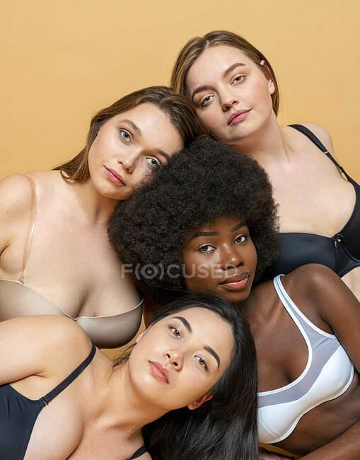 Les jeunes femmes regardant tout en s'appuyant les unes sur les autres sur fond jaune — Photo de stock