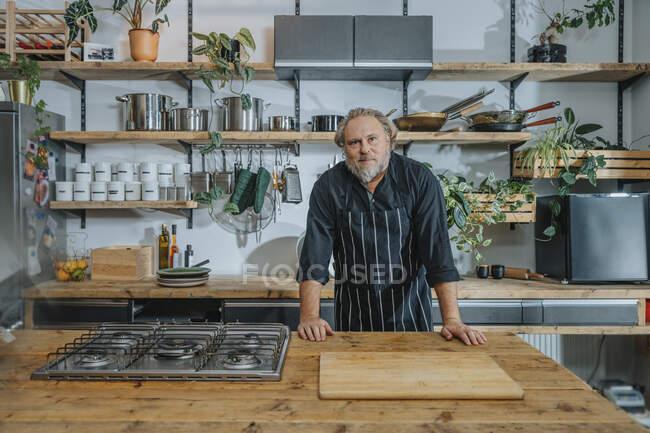 Довірливий дорослий шеф-кухар дивився на кухню, стоячи на стоянці. — стокове фото