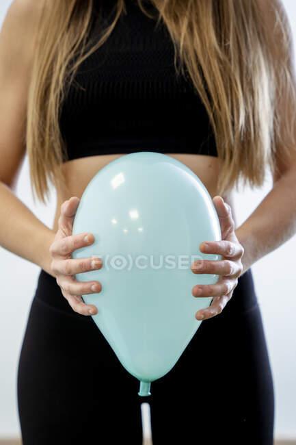 Partera sosteniendo globo azul contra el abdomen - foto de stock