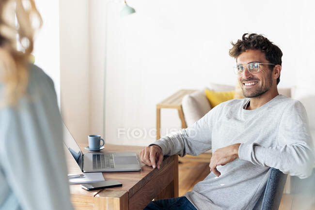 Усміхнений чоловік у окулярах, дивиться на свою дівчину, коли сидить у себе вдома. — стокове фото