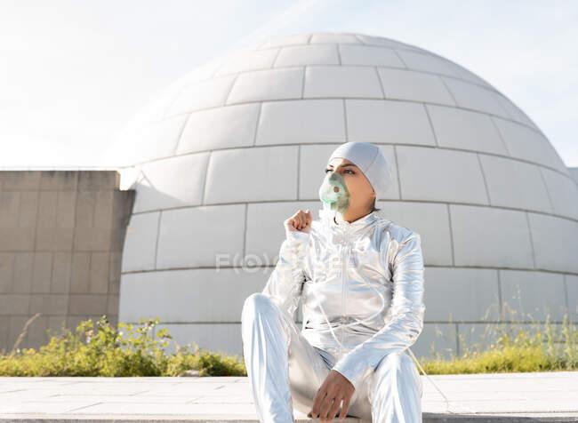 Mujer con traje protector y máscara de oxígeno mirando hacia otro lado mientras está sentada contra iglú - foto de stock