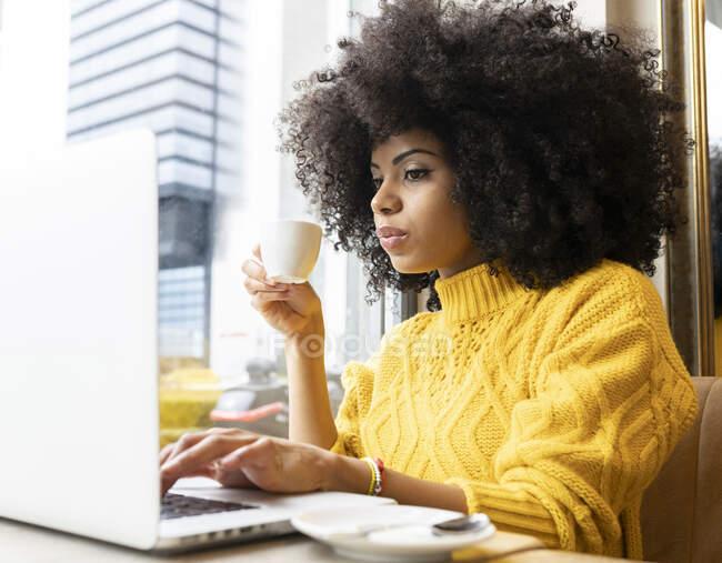 Mujer joven bebiendo café mientras trabaja en el ordenador portátil en la cafetería - foto de stock