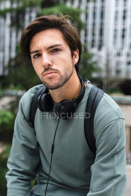 Bello giovane studente universitario maschio con le cuffie al campus — Foto stock