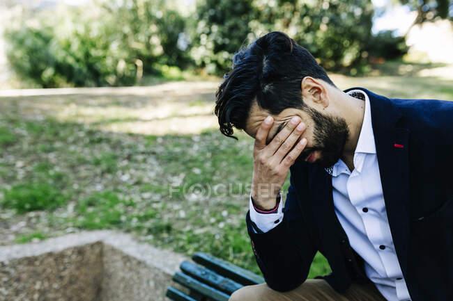 Empresario con la cabeza en las manos sentado en el parque público - foto de stock