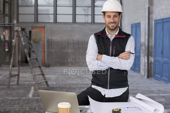 Architecte masculin confiant avec les bras croisés debout à table dans le bâtiment — Photo de stock