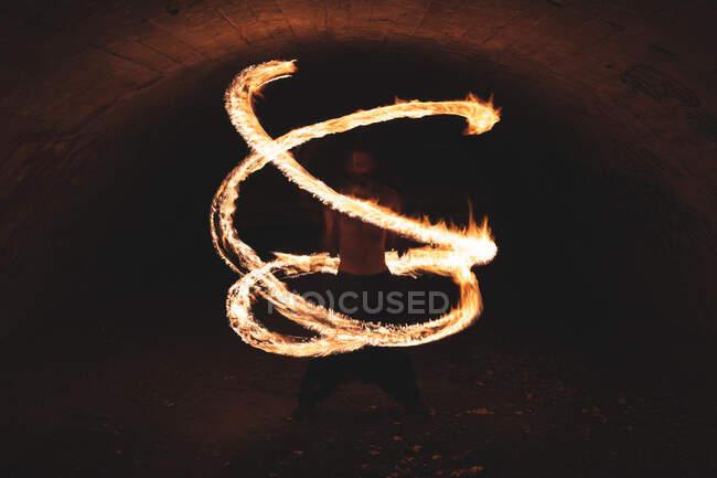 Joven realizando arte de fuego en túnel - foto de stock