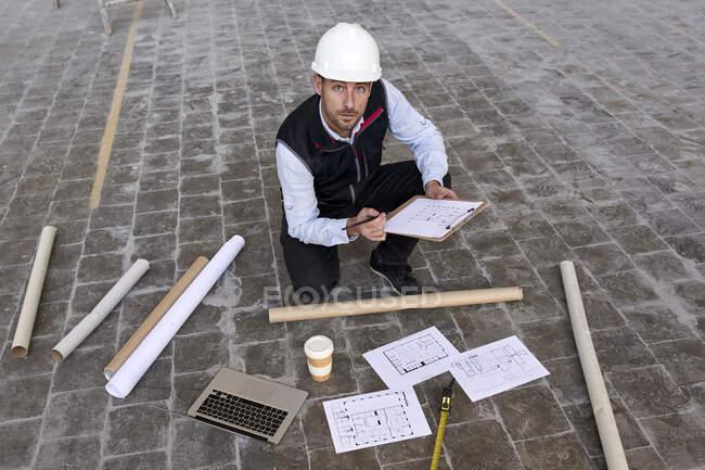 Homme ingénieur tenant le plan du site tout en s'agenouillant sur le sol dans le bâtiment — Photo de stock