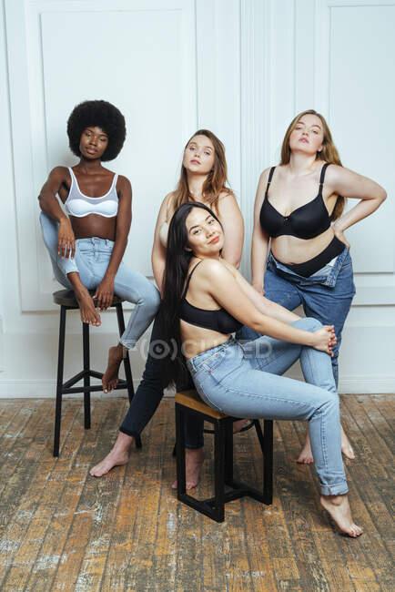 Groupe multi-ethnique confiant de femmes en soutien-gorge et jeans posant contre le mur — Photo de stock