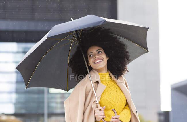 Усміхнена жінка в куртці стоїть, тримаючи парасольку під дощем. — стокове фото