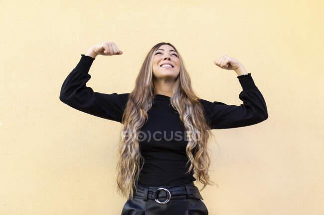 Mujer joven con el pelo largo flexionando los músculos mientras mira hacia arriba contra el fondo beige - foto de stock
