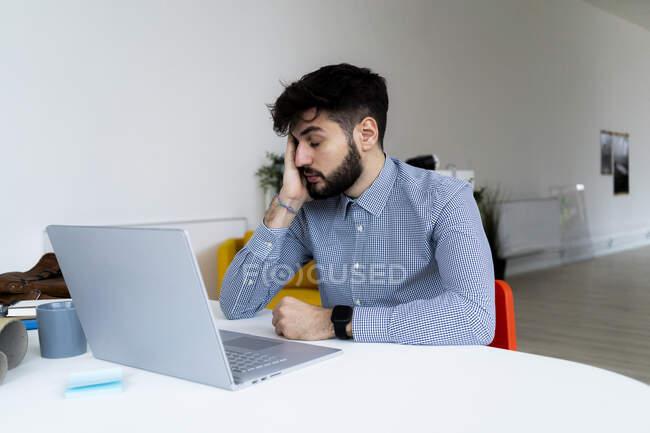 Hombre de negocios cansado mirando el ordenador portátil en la oficina creativa - foto de stock