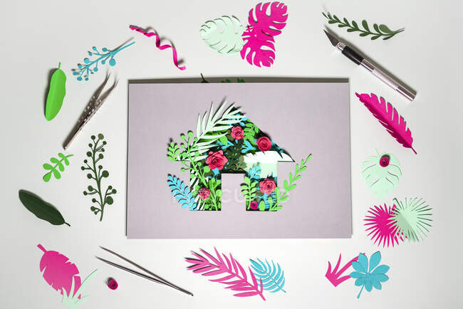 Paper craft of Eco home with plants and flowers amidst scraps on white background — Stock Photo