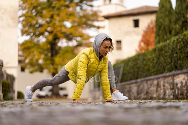 Mujer mirando hacia otro lado mientras hace ejercicio en el sendero - foto de stock