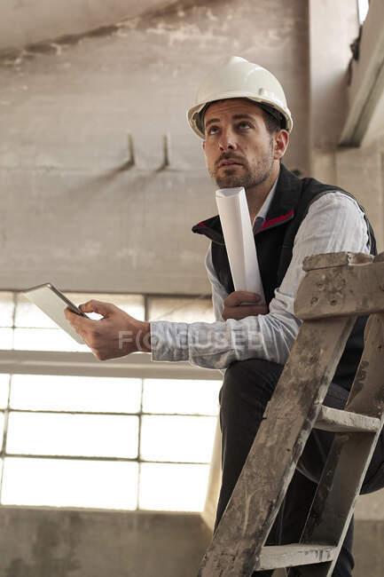 Ingénieur masculin avec tablette numérique et plan directeur contemplant tout en se tenant debout dans la construction sur le site — Photo de stock