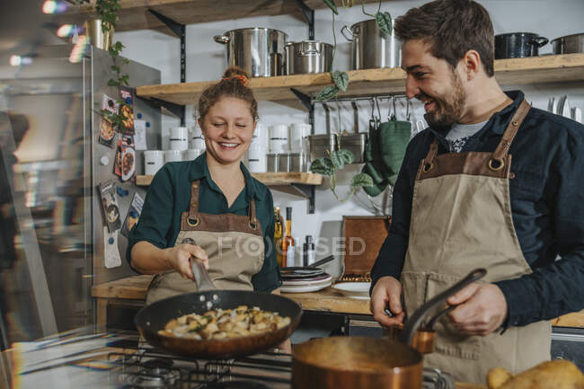 Молодий шеф - кухар, який навчається перемішувати їжу на сковороді, стоячи біля колеги на кухні. — стокове фото