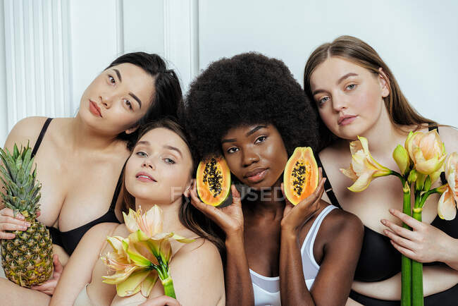 Multi-ethnic group of female models in lingerie holding fruit and flowers against white wall — Stock Photo