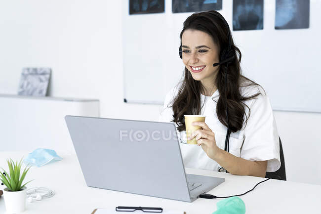 Happy female doctor consulting online through laptop at desk — Stock Photo