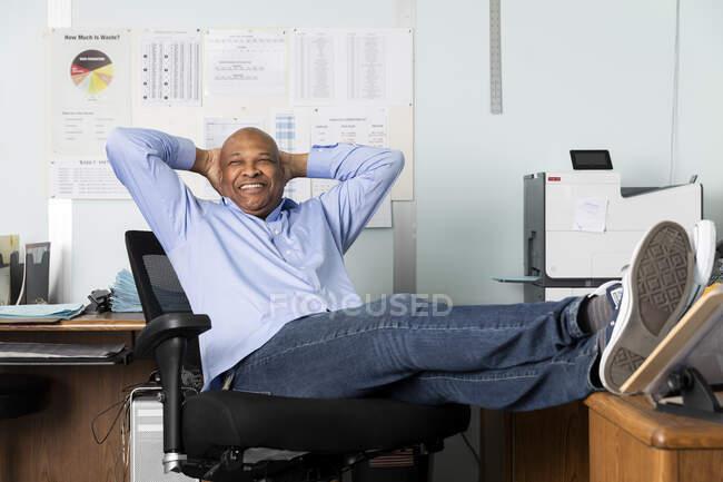 Веселий керівник, який сидить з руками позаду у друкарні. — стокове фото