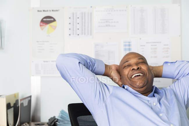 Весела працівниця з руками за головою сміється, сидячи в друкарні. — стокове фото
