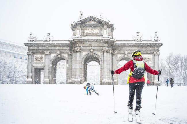Uomo e donna sciano sulla neve contro la Porta Alcala durante Storm Filomena nel 2021 a Madrid, Spagna — Foto stock