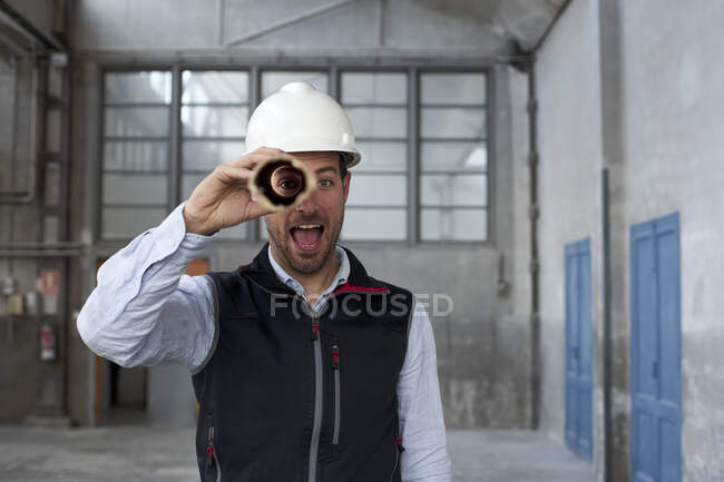 Male architect with mouth open looking through cardboard while standing in building — Stock Photo