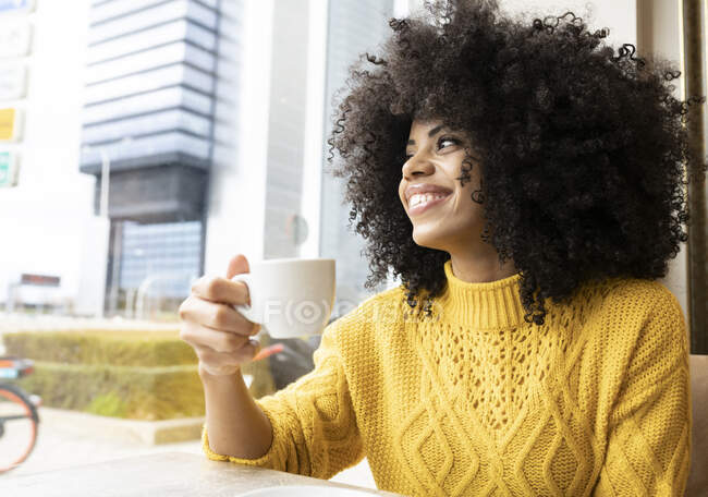 Smiling woman looking away while drinking coffee sitting at cafe — Stock Photo