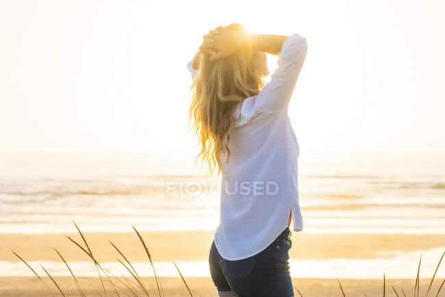 Жінка з руками позаду голови стоїть на пляжі під час заходу сонця. — стокове фото