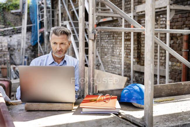 Зрілий інженер працює над ноутбуком, сидячи на будівельному майданчику. — стокове фото