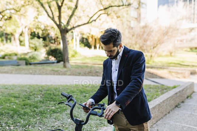 Бізнесмен за допомогою мобільного телефону стоїть на велосипеді в парку. — стокове фото