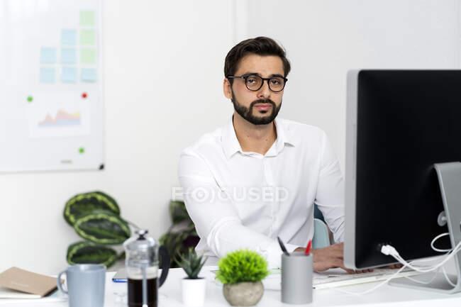Jeune homme d'affaires à lunettes assis devant l'ordinateur sur le bureau au travail — Photo de stock