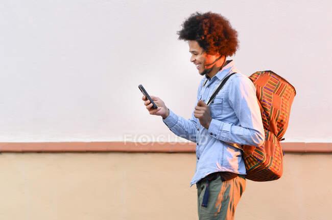Giovane sorridente con lo zaino utilizzando lo smartphone mentre in piedi contro il muro al tramonto — Foto stock