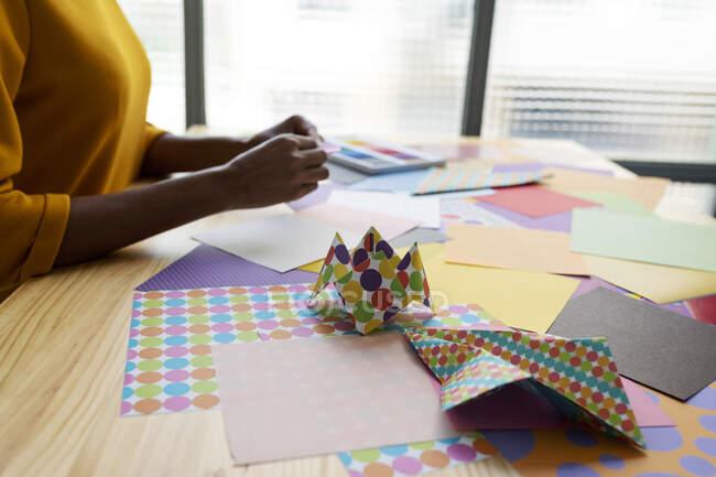Origami artista sentado en estudio plegable papel colorido - foto de stock