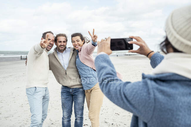 Group of friends taking smart phone photos at beach — Stock Photo