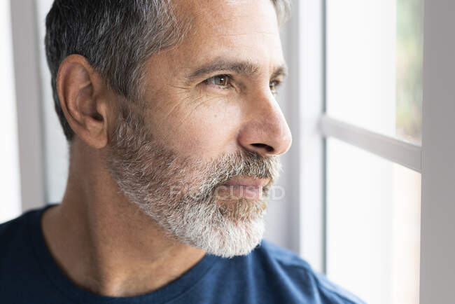 Close-up of man looking away while standing at home — Stock Photo