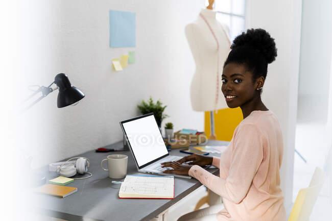 Diseñador de moda sonriente usando el ordenador portátil mientras está sentado en casa oficina - foto de stock