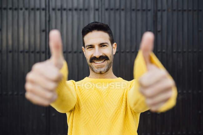 Feliz hombre mostrando los pulgares hacia arriba mientras está de pie contra la pared negra - foto de stock
