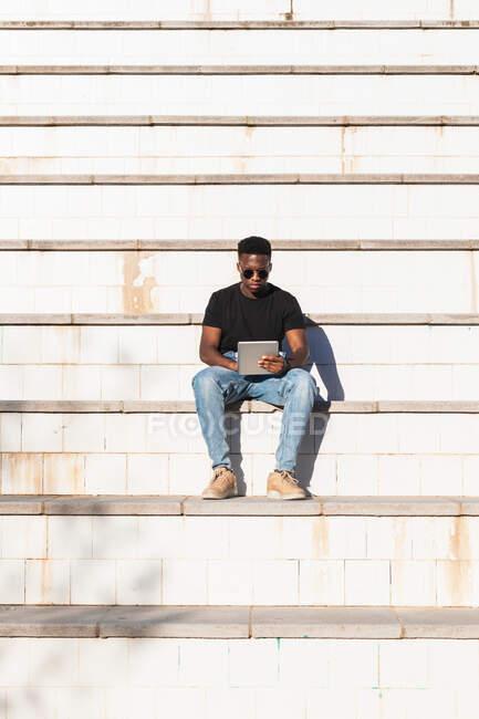 Hombre joven usando tableta digital mientras está sentado en la escalera durante el día soleado - foto de stock