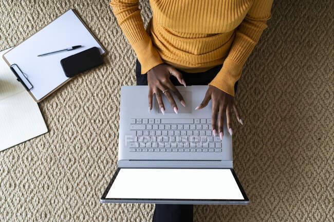 Молодая женщина с ноутбуком, сидя дома на ковре — стоковое фото
