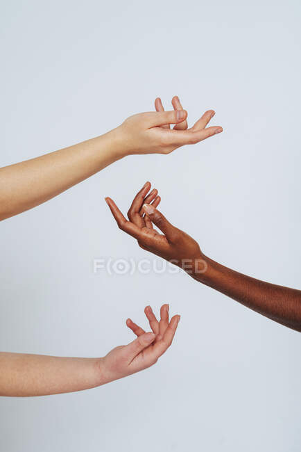 Women stretching hands toward each other against white background — Stock Photo