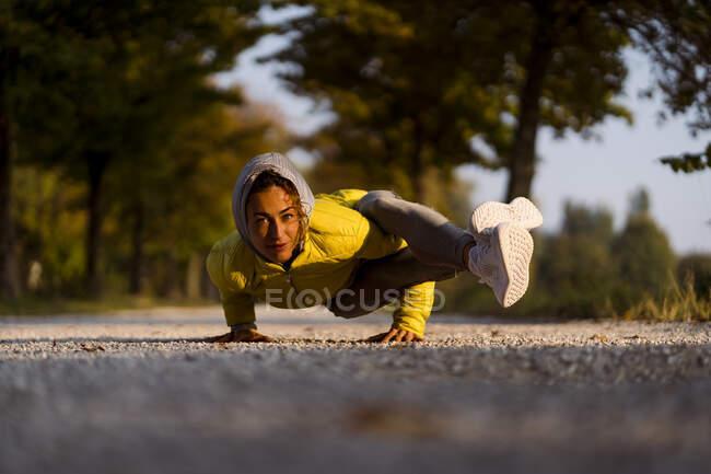 Deportista sonriente haciendo pie de manos mientras hace ejercicio en la carretera - foto de stock