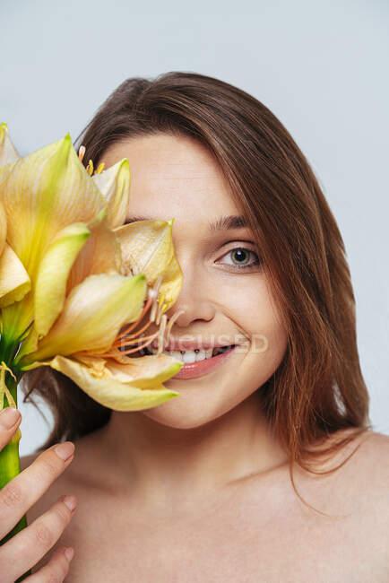 Усміхнена жінка покриває обличчя кучкою квітів, стоячи навпроти білого фону. — стокове фото