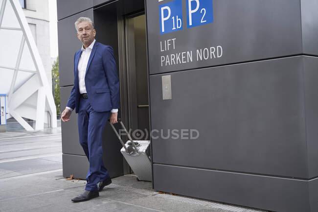 Hombre de negocios senior con equipaje de ruedas que sale del ascensor en la parada de autobús en la ciudad - foto de stock