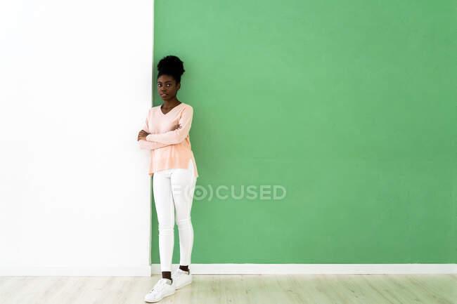 Молода жінка стоїть зі схрещеними руками на стіні. — стокове фото