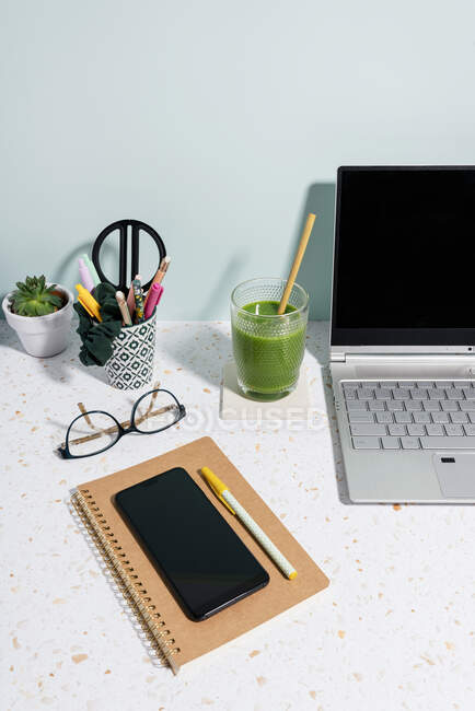 Laptop, healthy green juice, book, mobile phone and succulent plant over desk at home — Stock Photo
