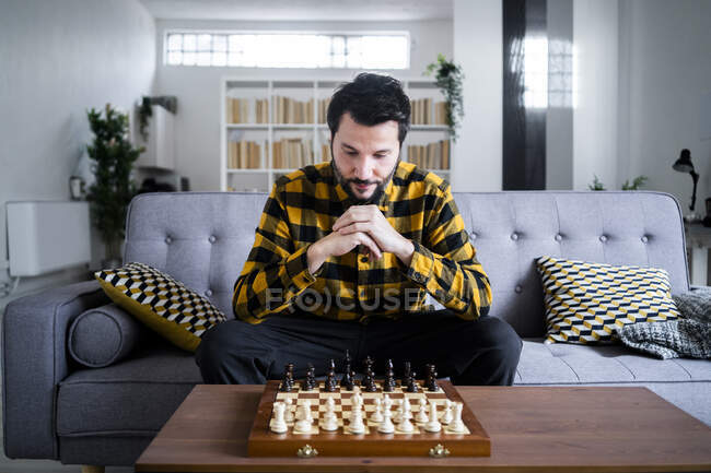 Man sitting on sofa in front of chess board — Stock Photo