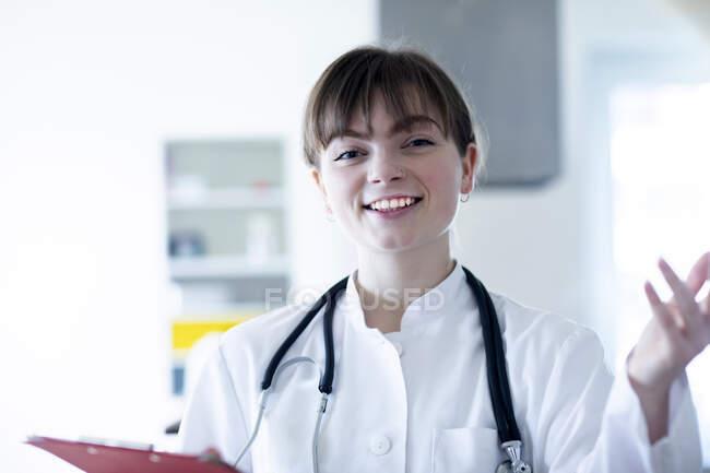 Sonriente doctora haciendo gestos mientras sostiene el portapapeles en el hospital - foto de stock