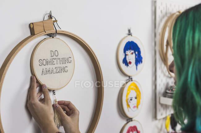 Primer plano de la mujer joven con el pelo teñido marco de bordado colgante en la pared - foto de stock